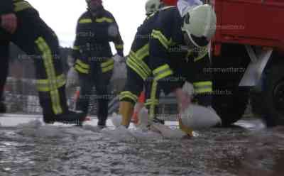 Überflutungen durch Tauwetter: Schmelzwasser überflutet Straße, Feuerwehr setzt Sandsäcke, hohe Temperaturen verursachen rasche Schneeschmelze: Hohe Gefahr für Auto Fahrer, mit Schaufeln werden Gräben gezogen