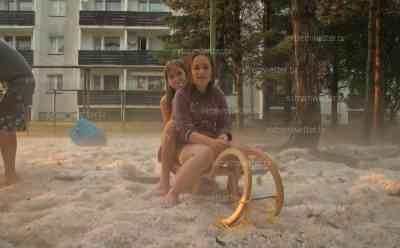 Hagelmassen bei Dachwig, Kinder fahren Schlitten im Hagel: Heftiges Unwetter bringt Hagelschollen