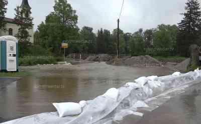 Land unter in Oberbayern: Sandsäcke gegen Wassermassen – Straße wird durch Überflutung unpassierbar – Feuerwehr muss Wall errichten: Gasthof rüstet sich mich liegenden Biertischen gegen Flut