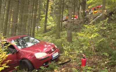 Spektakulärer Abflug nach Unfall: VW kollidiert mit Nissan, Nissan fliegt mehrere Meter tief und etliche Meter weit in Wald, Rettungsdienst kann nur über Leiter zum Unfallwagen, nur ein Baum stoppt den weiteren Abflug: Rettungsdienst muss über Leitern zum verunfallten Fahrzeug (on tape), VW Fahrer muss durch den Wald zum Rettungsdienst gebracht werden