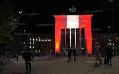 Nach Terroranschlag: Österreich zeigt Solidarität, Nationalflagge leuchtet mit Schweinwerfern an Befreiungsdenkmal, Österreicher gedenken auch dem deutschen Opfer: Österreichische Nationalflagge rot-weiß-rot leuchtet am Abendhimmel zum Beginn des Lock Down in Innsbruck