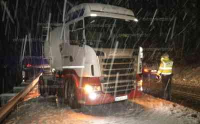 Schneechaos: querstehende LKW, Polizei regelt Verkehr im dichten Schneetreiben, selbst PKW Fahrer kamen kaum mehr voran: über 10 cm Neuschnee auf Straßen, LKW Räder drehen im Stand durch, LKW droht in Leitplanke zu rutschen